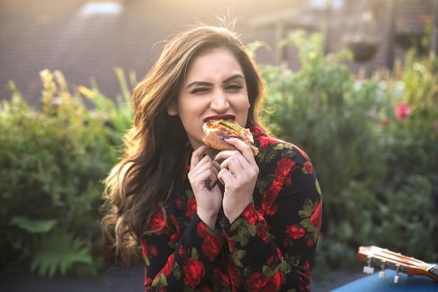 Graciosa comiendo pizza en una terraza Foto Premium