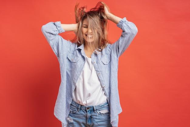 Graciosa, linda chica divirtiéndose mientras juega con el pelo aislado en una pared roja Foto gratis
