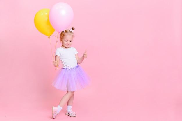 Graciosa niña en camiseta blanca y falda lila con globos sobre fondo rosa. retrato infantil con espacio para texto. Foto Premium
