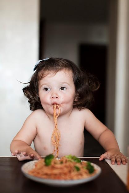 Graciosa niña comiendo espagueti Foto gratis