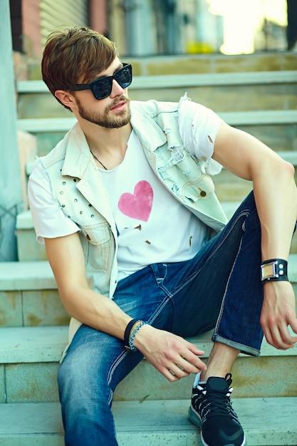 Gracioso sonriente hipster hombre guapo en elegante ropa de verano en la calle con gafas de sol Foto gratis