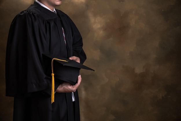 Graduación, el estudiante tiene sombreros en la mano durante los graduados de éxito inicial Foto Premium