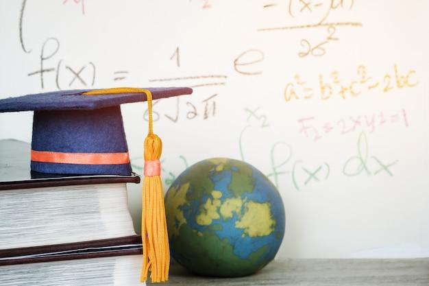 Graduado de educación birrete azul sombrero en libro de texto con fórmula ecuación matemáticas Foto Premium