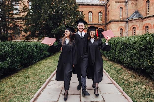 Graduados exitosos con su diploma caminando en el jardín universitario Foto Premium