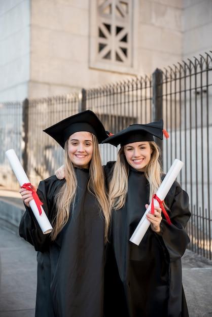 Graduados universitarios de tiro medio sonriendo Foto gratis
