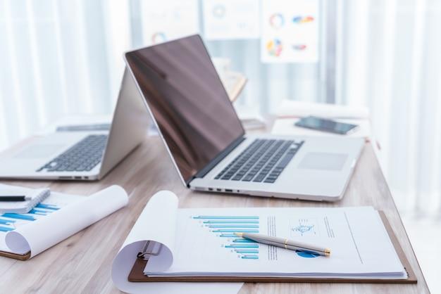 Gráficos financieros sobre la mesa con el ordenador portátil Foto gratis