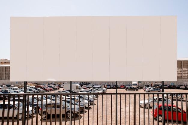Gran cartelera en blanco cerca del estacionamiento. Foto gratis