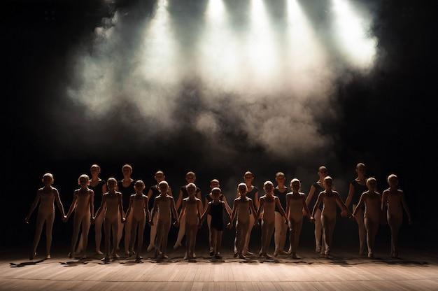 Un gran grupo de niños tiene una reverencia al final de la actuación. Foto Premium