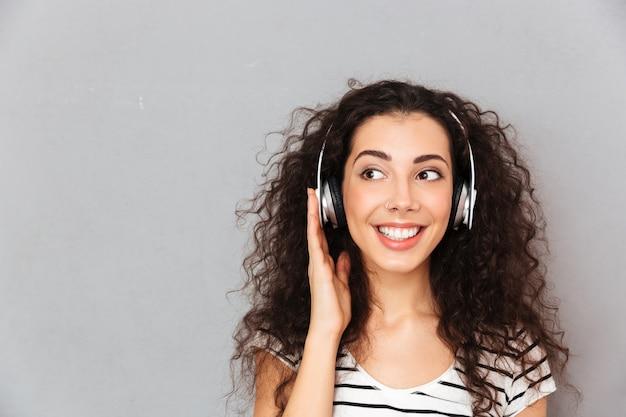 Gran imagen de mujer caucásica rizada en camiseta a rayas en auriculares disfrutando de la música a través de un dispositivo moderno mientras descansa Foto gratis