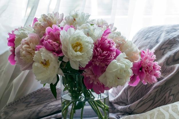 Un gran ramo de peonías en un jarrón está sobre la mesa Foto Premium