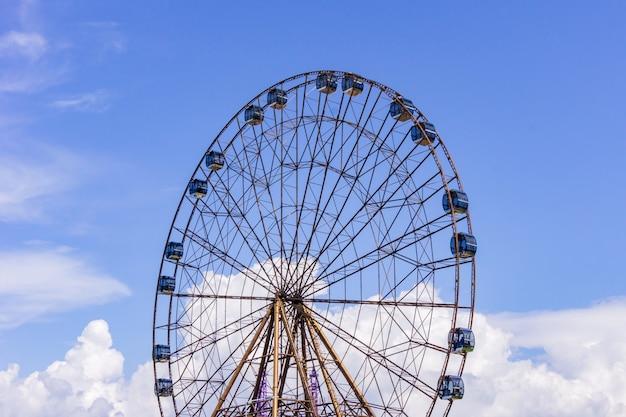 Gran rueda de la fortuna atraktsion en el fondo de un hermoso cielo azul con nubes Foto Premium
