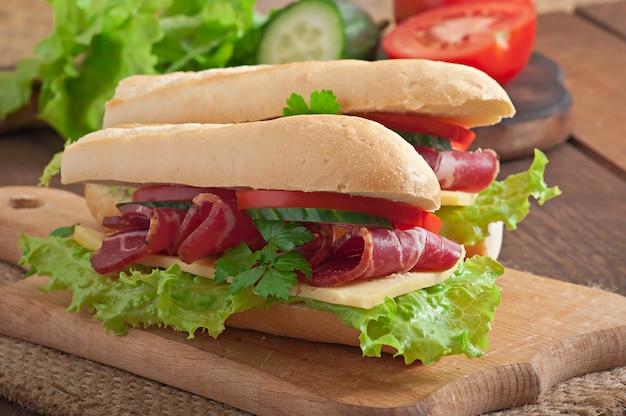 Gran sándwich con carne cruda ahumada sobre una superficie de madera Foto gratis