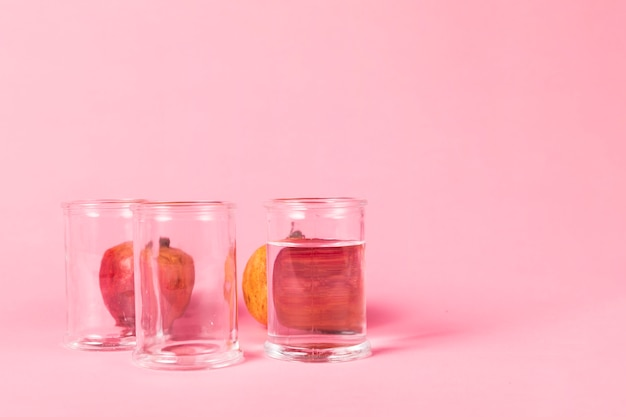 Granada detrás de vasos llenos de agua Foto gratis
