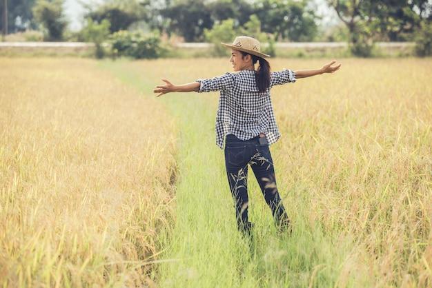 El granjero está en el campo de arroz y cuida su arroz. Foto gratis