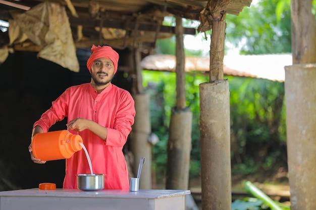 Granjero indio o lechero recogiendo leche en la granja lechera Foto Premium