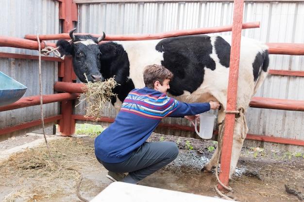 Granjero ordeñando a una vaca Foto gratis