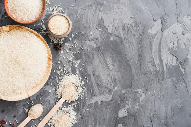 Grano de arroz crudo orgánico en placa de madera; tazón y cuchara sobre papel tapiz de hormigón texturado Foto gratis