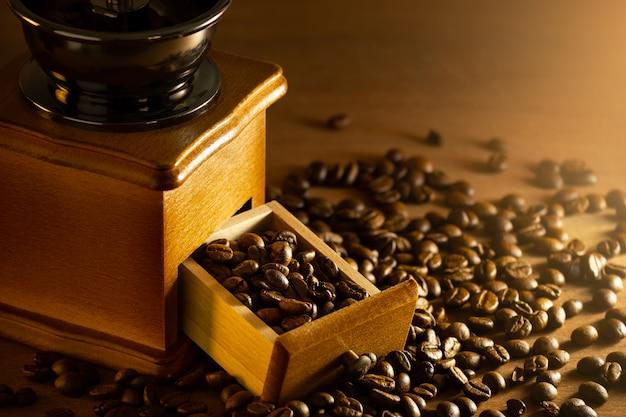 Grano de café en la bandeja del molinillo en la mesa y la luz de la mañana. Foto Premium