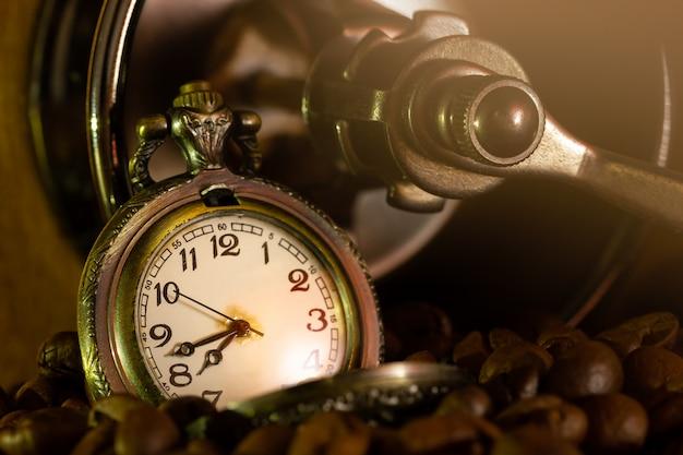Grano de café y reloj de bolsillo en molinillo manual sobre mesa. primer plano y copyspace. hora del café en la mañana. Foto Premium