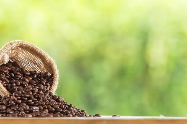 Grano de café en el saco en la mesa de madera contra el fondo verde de desenfoque de grunge Foto gratis