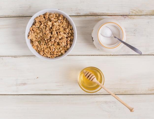 Granola con semillas de calabaza; leche en polvo en jarra y miel en mesa de madera Foto gratis