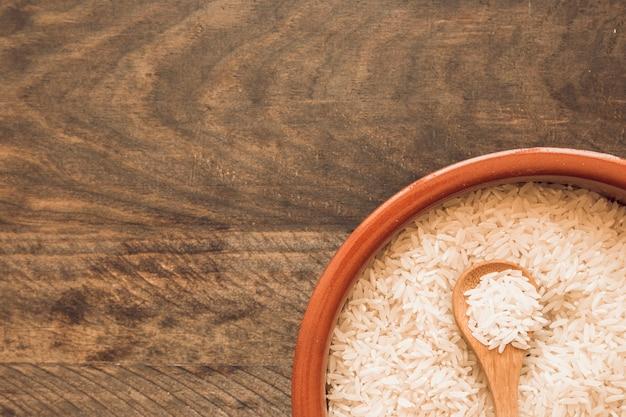 Granos de arroz crudo con cuchara de madera sobre el fondo de madera Foto gratis