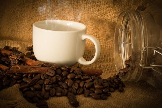 Granos de café y café de la taza en el saco de tela seleccionar enfoque, tono de color vintage o tono oscuro Foto Premium