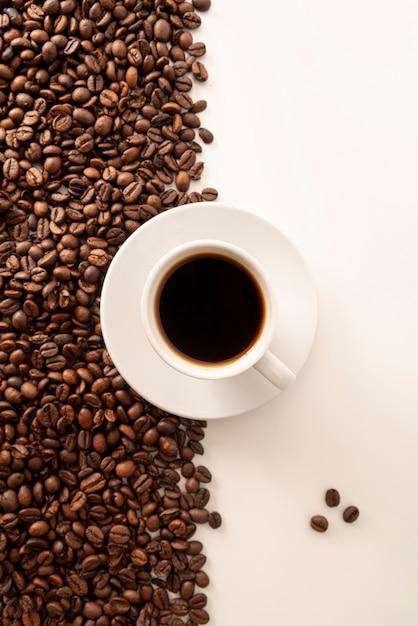Granos de café contrastados fondo y taza Foto gratis