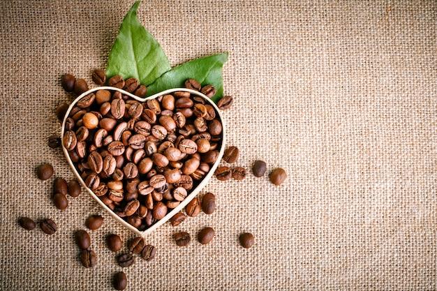 Granos de café fritos se encuentran en forma de corazón en tablas de madera y arpillera. Foto Premium