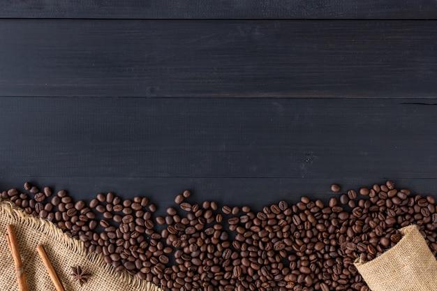 Granos de café en saco de la arpillera en viejo fondo de madera. vista superior Foto Premium