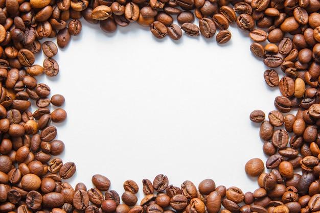 Granos de café sobre un fondo blanco. vista superior. espacio para texto Foto gratis
