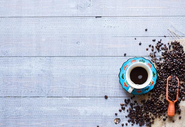 Granos de café y taza de café con otros componentes sobre fondo de madera diferente. espacio libre para texto Foto Premium