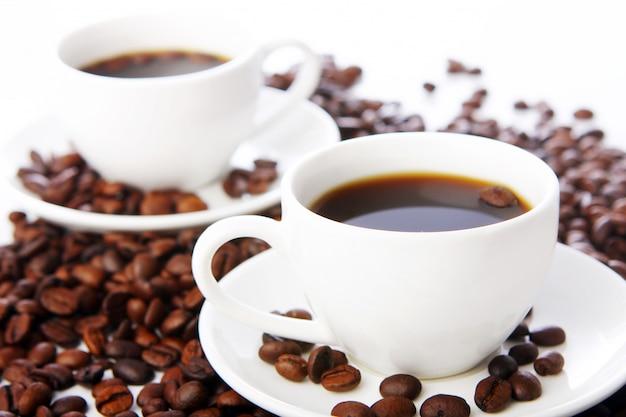 Granos de café con tazas blancas Foto gratis