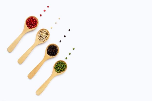 Granos de pimienta verde, rojo, blanco y negro con cuchara de madera en blanco Foto Premium