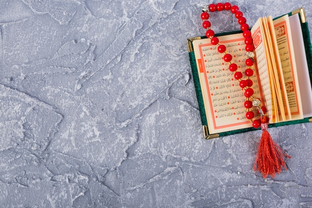 Granos de rosario rojo brillante en un sagrado kuran abierto sobre el fondo texturizado concreto Foto gratis