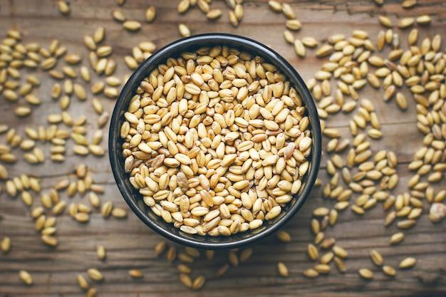 Granos de trigo en un tazón y palomitas de maíz en un tazón, semilla de trigo rústica Foto gratis