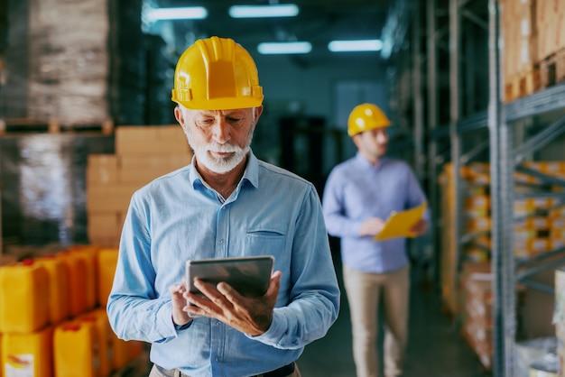 Grave auditor adulto mayor de raza caucásica en ropa formal y con casco protector amarillo en la cabeza usando tableta para controlar mercancías Foto Premium