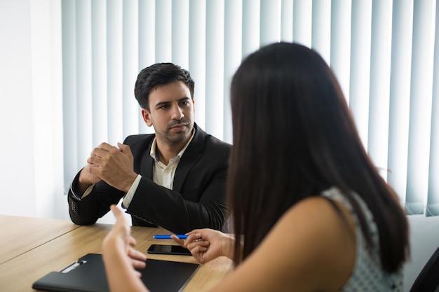 Grave ejecutivo escuchando a compañera o empleada. Foto gratis