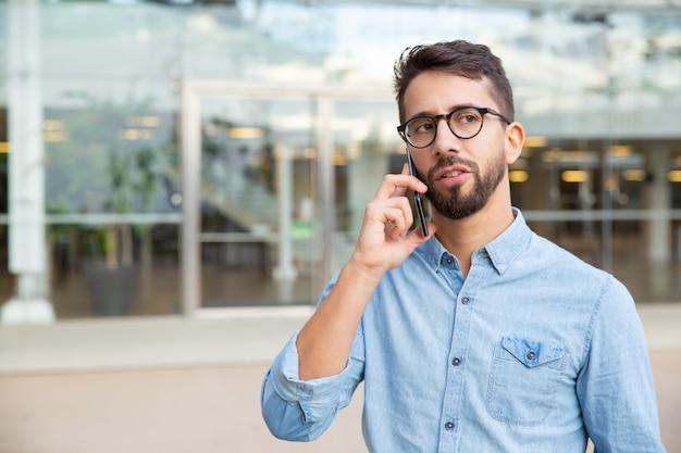 Grave joven hablando por teléfono inteligente Foto gratis