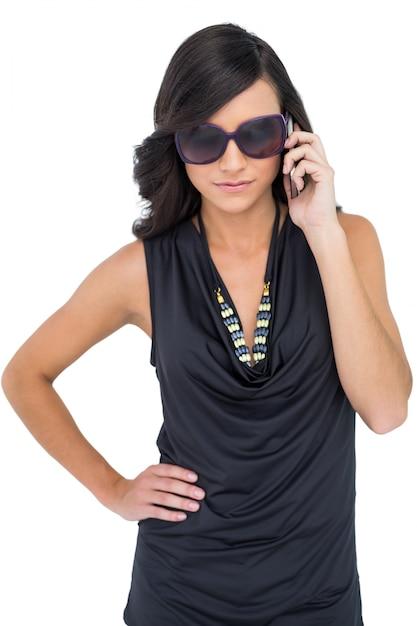 254324f8a7 Grave morena elegante usando gafas de sol en el teléfono   Descargar ...