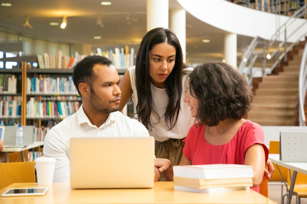 Graves estudiantes sentados a la mesa en la biblioteca con laptop Foto gratis
