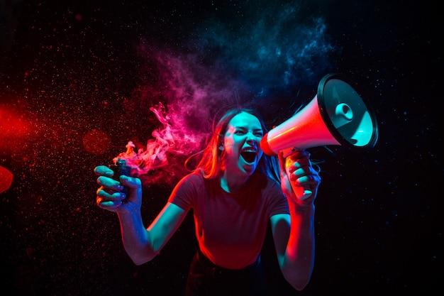 Gritando con megáfono. mujer joven con humo y luz de neón sobre fondo negro. vista de ojo de pez muy tensada, gran angular. Foto gratis