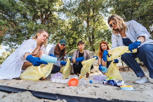 Grupo de activistas amigos recogiendo residuos plásticos en la playa. conservación del medio ambiente. Foto gratis
