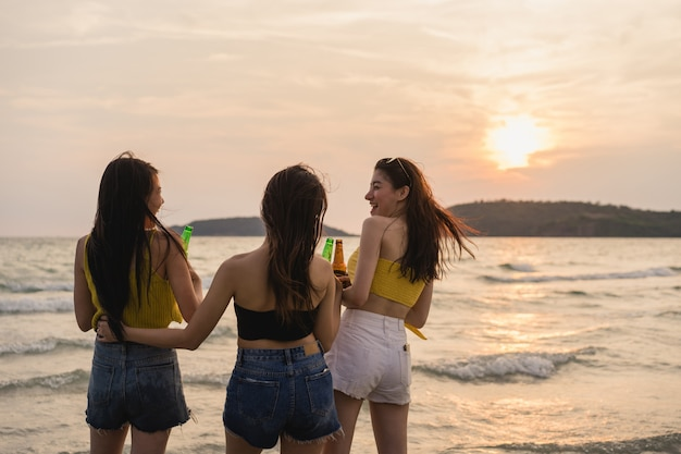 Grupo de adolescentes asiáticas con fiesta celebrando en la playa Foto gratis