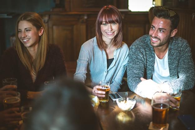 Grupo de adolescentes divirtiéndose en un pub Foto Premium