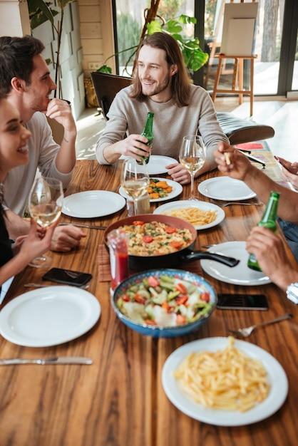 Grupo de amigos alegres comiendo y hablando en la mesa Foto Premium