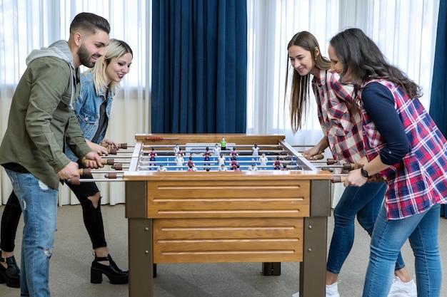 Grupo de amigos alegres jugando futbolín Foto Premium