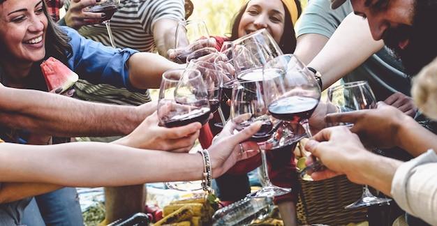 Grupo de amigos animando y brindando con copas de vino tinto en la fiesta Foto Premium