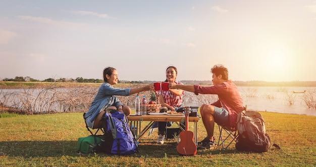 Un grupo de amigos asiáticos tomando café y pasando el tiempo haciendo un picnic en las vacaciones de verano. son felices y se divierten en las vacaciones. Foto Premium
