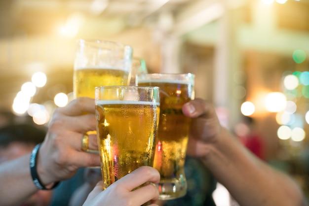Un grupo de amigos con bebidas en un club nocturno. los jóvenes están disfrutando Foto Premium